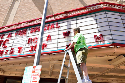 A woman places letters on a movie theater marquee