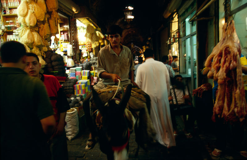 Syria - Aleppo - A man rides a donkey through the Souk