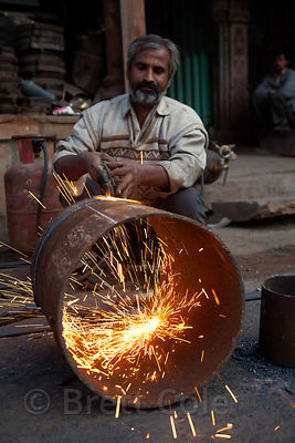 A welder cuts a large metal cylinder, Jodhpur, Rajasthan, India