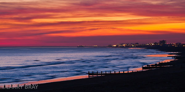 Panoramic view of Shoreham beach towards Worthing Pier at sunset in Shoreham-by-Sea, West Sussex, UK