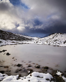 Storm clouds over a frozen Loch Allt an Daraich with the summit of Creag Dhubh in the distance. Scottish Highlands, Scotland,...