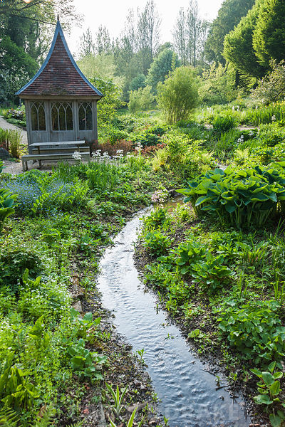 Summerhouse surrounded by bog and streamside planting including hostas, candelabra primulas and yellow flag irises with avenu...