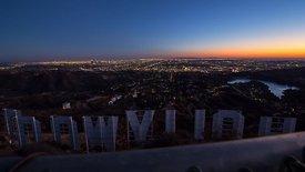 Bird's Eye: Moving Shot Looking Over a Fence Top at the Hollywood Sign & Los Angeles at Dusk