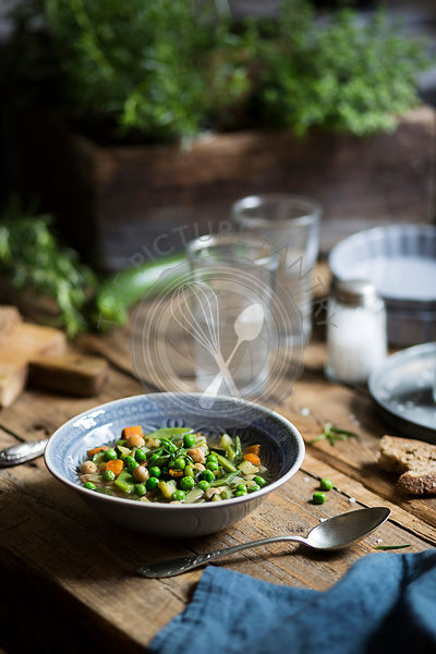 Soup with peas, carrots, zucchini and chickpeas on a rustic table