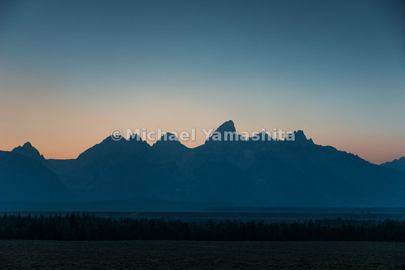 Sunset along Teton Park Road. Grand Teton National Park, Wyoming...Jagged peaks of the Teton Range, lush meadows, dense fores...