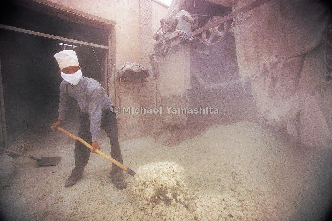 Dangerous asbestos dust pollutes the air around a worker in Zhangye.