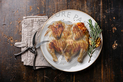 Grilled fried roast Chicken Tabaka on plate on wooden background