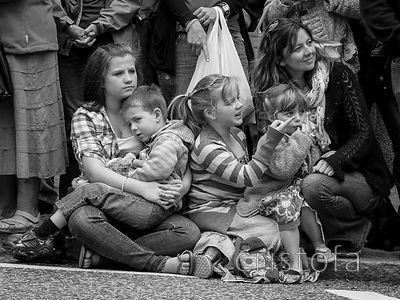 a family watches the parade at the Golowan Festival in Penzance