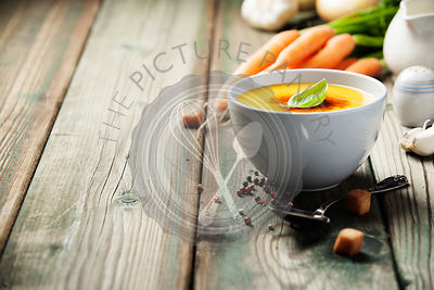 Vegetable cream soup in bowl over old wooden background, copy space