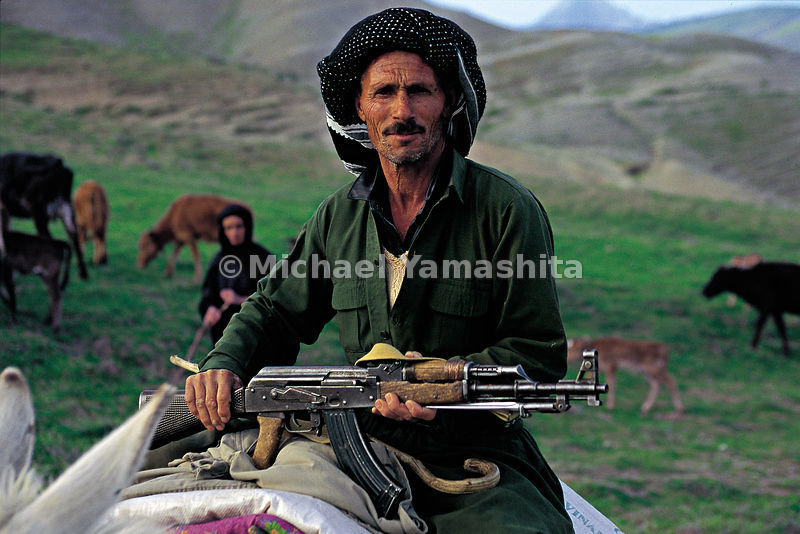 With his AK-47 in hand, a Kurd shepherd leads his flock to pasture. Ruwanduz, Iraq.