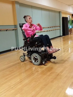 Young woman using a power wheelchair exercising in a dance studio