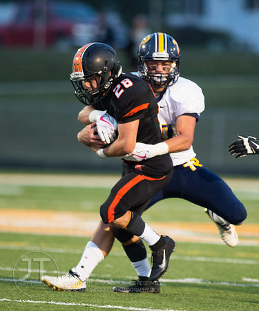 Iowa City Regina's Ryan Schott (28) forces a fumble by Solon's Hunter Kula (28) during the first half of play in Solon on Fri...
