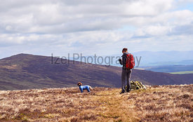A hiker checking their position on a GPS map at the cairn marking Coomb Height in the English Lake District, UK.