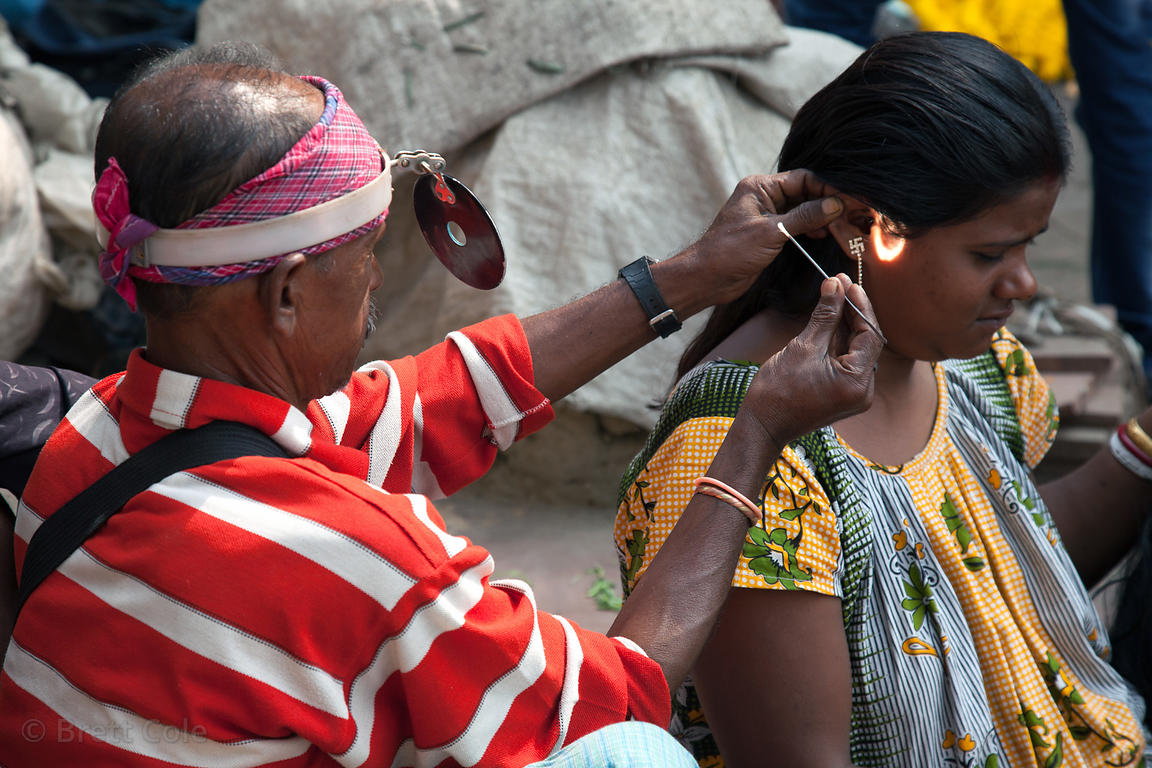 A man cleans a woman's ear, using a CD to focus light, on Armernian Ghat along the Hooghly River, Kolkata, India.
