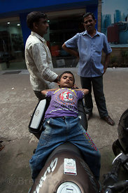 A boy naps on his father's motor scooter, Newmarket, Taltala, Kolkata, India
