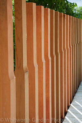 Shaped vertical timber fence posts in The Marshalls Living Street garden, designed by Ian Dexter at the RHS Chelsea Flower Sh...
