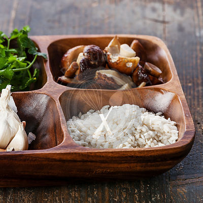 Raw white rice in wooden bowl with ingredients for risotto with wild mushrooms