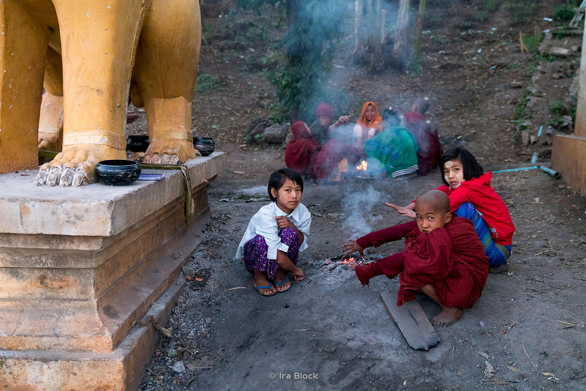 Novice monks sit around a fire at Htet Eain Cave Monastic Education Schools near Nyaungshwe in Myanmar.