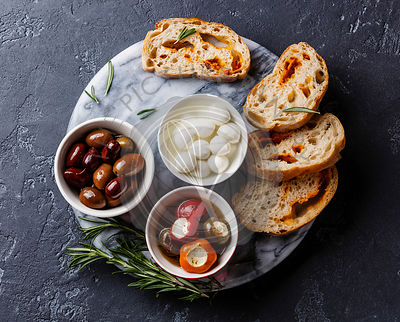 Olives, stuffed Peppers, mini Mozzarella cheese and sliced Ciabatta bread on dark background