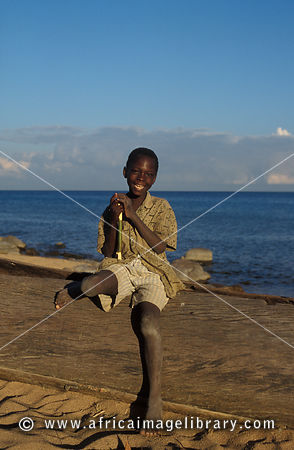 boy sitting on a dugout canoe on the beach, Likoma Island, Lake Malawi, Malawi