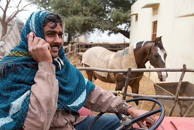 A farmer talks on his mobile phone while sitting proudly on his tractor in front of his favorite personal horse, Killa villag...