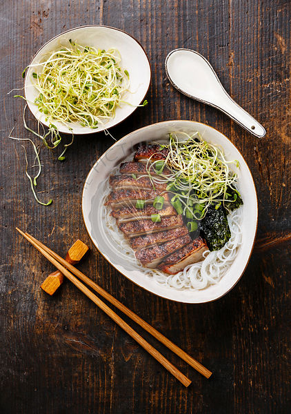 Rice noodles bowl with Peking Duck and sprouts on wooden background