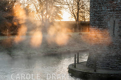Early morning sun illuminates mist rising from spring water tumbling into the moat around the Bishop's Palace in Wells on a N...
