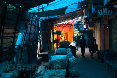 A pandal with an idol of the goddess Kali is seen before sunrise on a street full of yet-to-open market stalls, Newmarket, Ko...