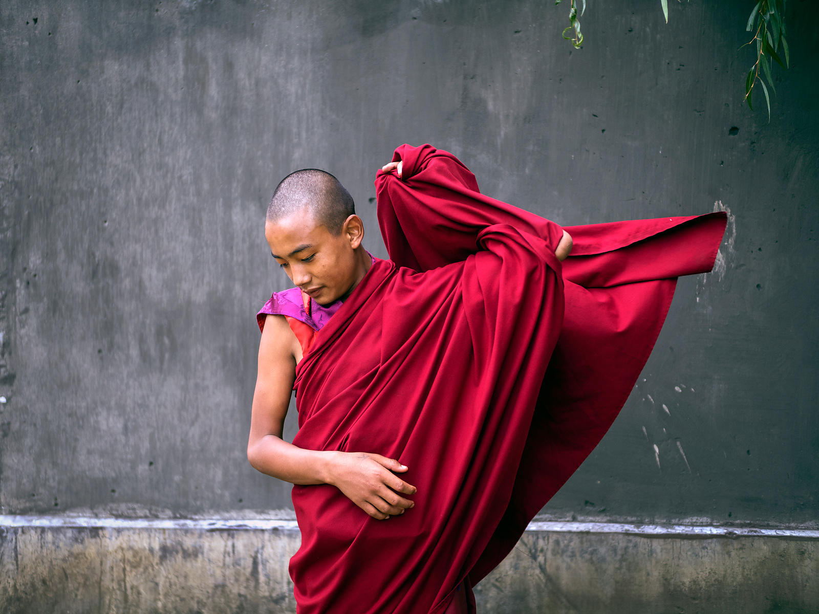 A young Buddhist monk adjusts his robe. This photograph was shot in a monastery in Bhutan
