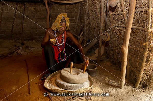 Mijikenda medicine man in his hut grinding maize, Ngomongo Village, Kenya