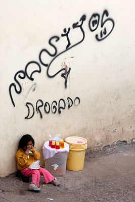 A 5 year-old girl tends to her mother's food stall - consisting of a bucket on the sidewalk - underneath graffiti on a street...