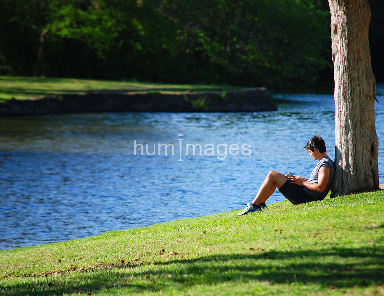 side view of man reading book in park by pond
