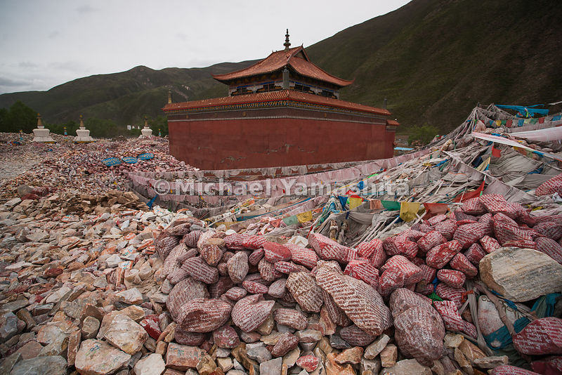 A woman adds her prayers to the growing mountain of more than a billion mani stones at Gyanamani Temple, in Yushu, an area ro...