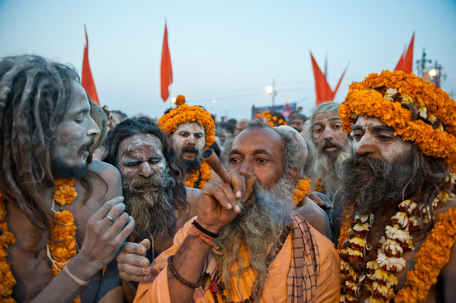 A saint smokes a pipe while others wait for their turn. This photograph was shot during a procession at the Kumbh Mela in All...