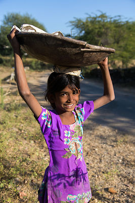 A farm girl carries a metal bowl on her head, Kharekhari village, Rajasthan, India