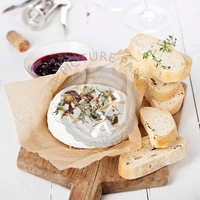 Baked Camembert cheese with thyme and toasted bread on wooden board