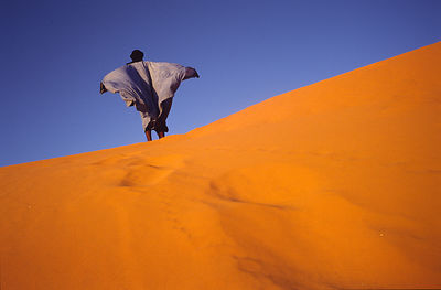 A man walks over a dune overlooking Chinguetti