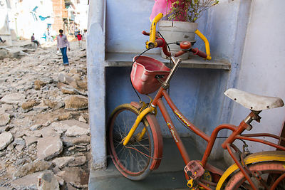Child's bike on a porch next to a street that is rubble as it waits to be resurfaced, Pushkar, Rajasthan, India