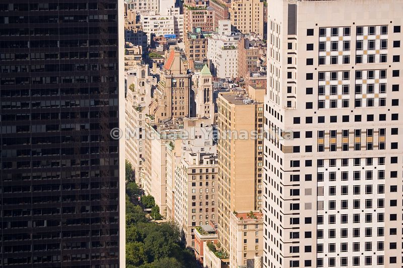 A peek around the corner of 9 West 57th St. reveals a hint of Central Park.  Manhattan, New York City.