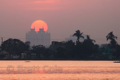 Sunset over the town of Chingrihata and the EM Bypass, from a remote footpath in the East Kolkata Wetlands, Kolkata, India.