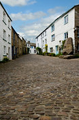 Looking up cobbled main street towards the Sedgewick Stone and the Sun Inn, in Dent, Yorkshire Dales National park near Sedbe...