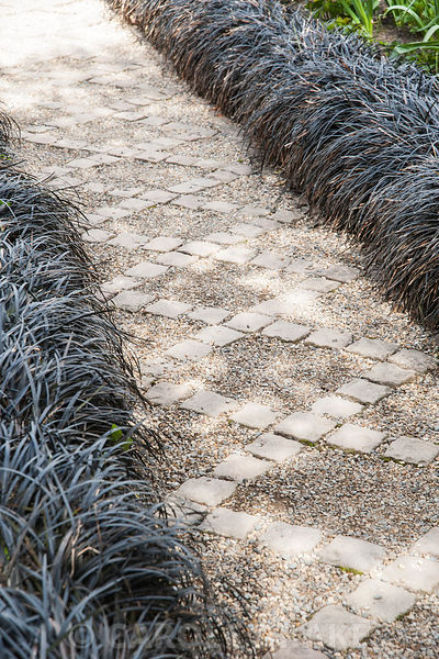 A path of stone setts and gravel in the Canal Garden is framed by black Ophiopogon planiscapus 'Nigrescens'. York Gate Garden...