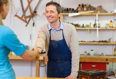 Carpenter shaking hands with client