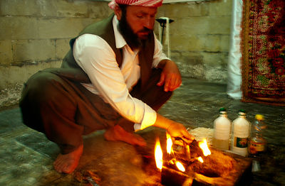 Yezidi priest lights a lamp