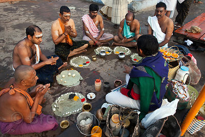 Hindu men perform prayers and rituals in honor of deceased relatives, Varanasi, India.