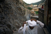 India - Rajasthan - A man ties his turban after bathing in the pool at The Surya Mandir (known as the Monkey Temple)