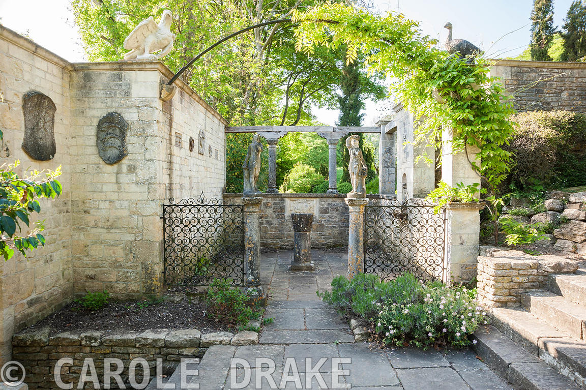 The Patio Garden, a small paved court, framed by wrought iron screens and a pair of Italian marble dancing figures. Iford Man...