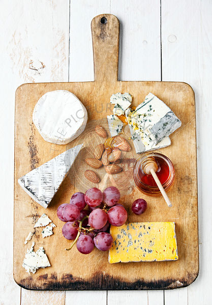 Assortment of various types of cheese on wooden board