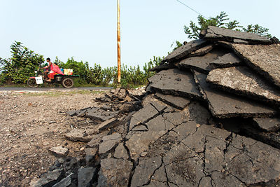 Piles of asphalt waiting to be melted down and recycled at a small facility near the Dhapa landfill, East Kolkata Wetlands, K...