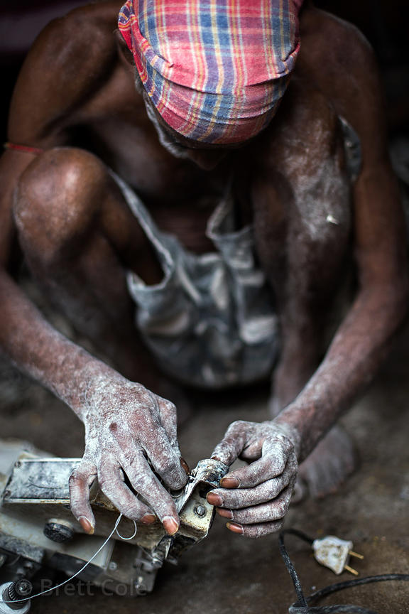 A man repairs a piece of equipment in a flour mill, Beniatola, Kolkata, India